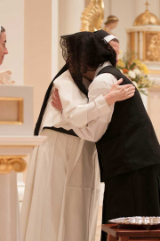 The postulant receives a Dominican pin and is welcomed by the Prioress General.