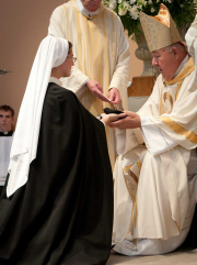 The novice receives the black veil from the bishop.