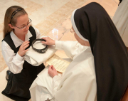 The Prioress General, calling the sister by her new name, gives each part of the habit to her.